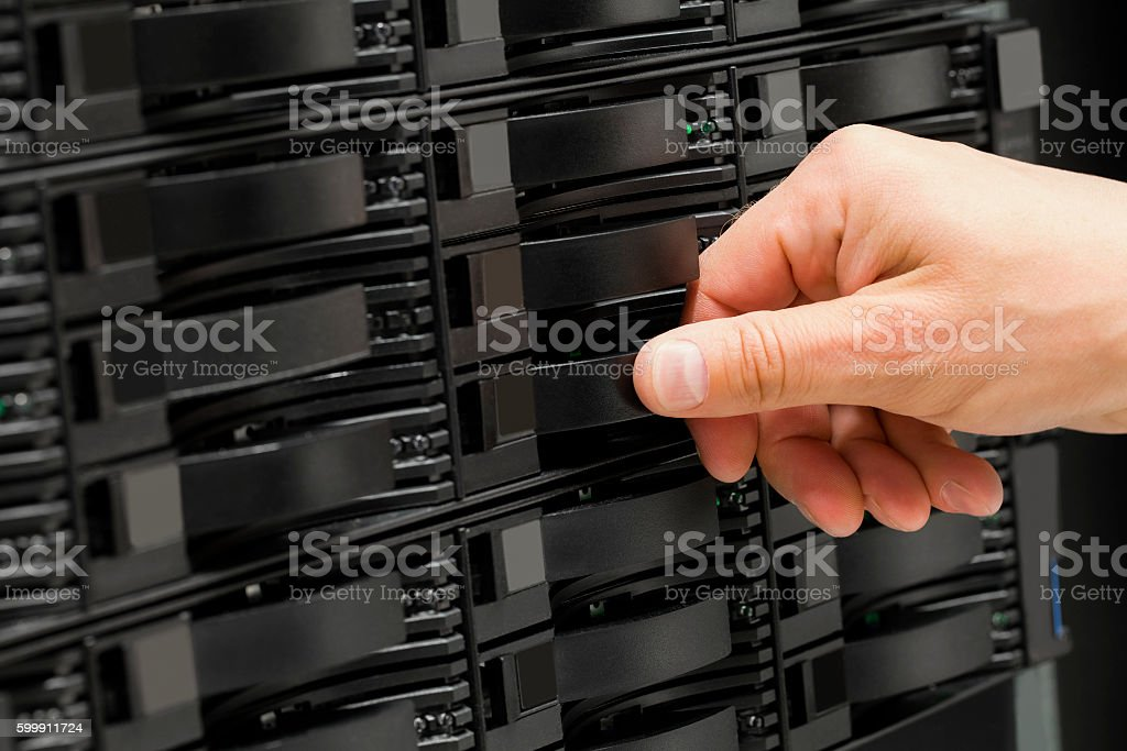 IT consultant replaces SAN harddrive in datacenter stock photo