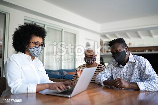 Consultant using laptop and giving advice to a couple at customer's house