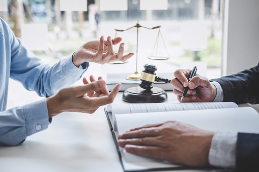istock Consultation and conference of Male lawyers and professional businesswoman working and discussion having at law firm in office. Concepts of law, Judge gavel with scales of justice 1160817640