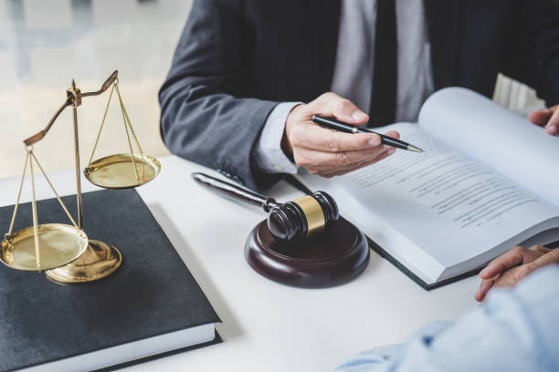 Consultation and conference of Male lawyers and professional businesswoman working and discussion having at law firm in office. Concepts of law, Judge gavel with scales of justice stock photo