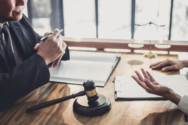 Consultation and conference of professional businesswoman and Male lawyers working and discussion having at law firm in office. Concepts of law, Judge gavel with scales of justice stock photo