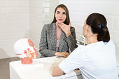 Consultation in cosmetology clinic. Female beauty doctor talking with patient. A young girl tells what she wants change in her face. Client shows on himself. Doctor listening carefully