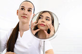 Consultation in cosmetology clinic. Female beauty doctor talking with patient. A young girl tells what she wants change in her face. Client shows on himself using mirror. Doctor listening carefully