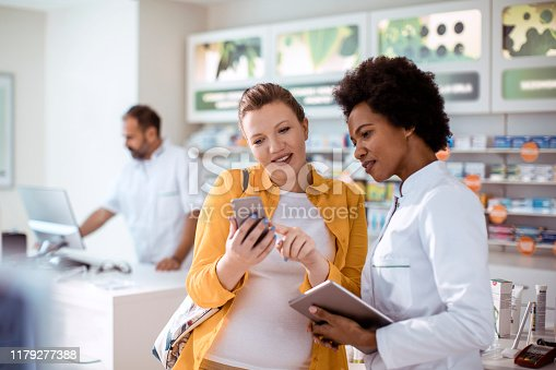 Close up of a pregnant woman consulting with her pharmacist