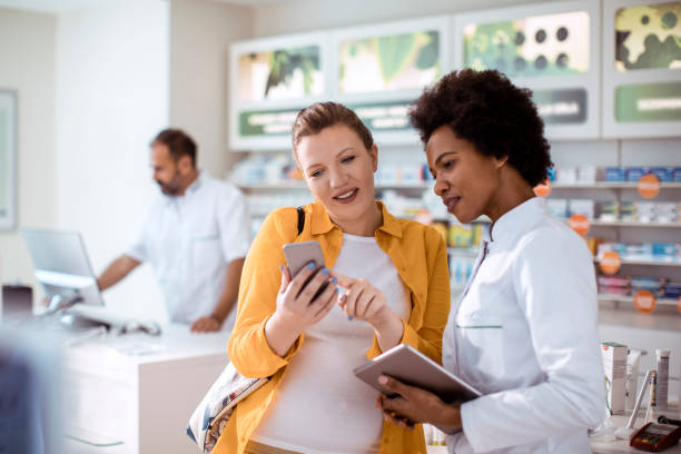Consultation Close up of a pregnant woman consulting with her pharmacist pharmacy stock pictures, royalty-free photos & images