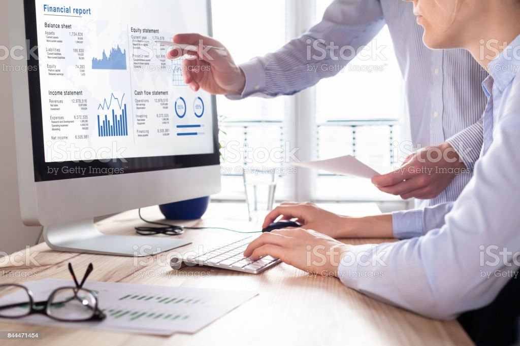 Consulting auditors auditing financial report on computer screen, business charts stock photo