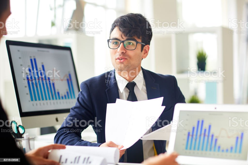 Consulting with colleague Young economist talking to colleague and explaining financial papers Adult Stock Photo