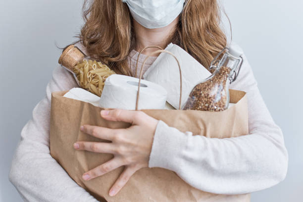 consumer buying panic about coronavirus covid-19 concept. people buying essentials in bulk at supermarkets concept. woman hold shopping bag with rolls of toilet paper, pasta and buckweat - carta igienica foto e immagini stock