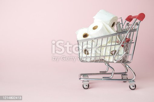 1136804881 istock photo Consumer panic corona virus concept. Toilet paper rolls in shopping cart abstract on pastel pink background. 1214802413