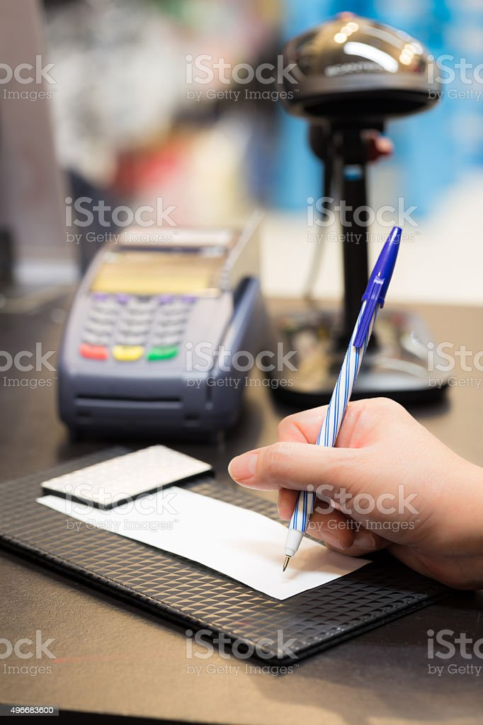 Consumer signing on a sale transaction receipt with Credit Card stock photo
