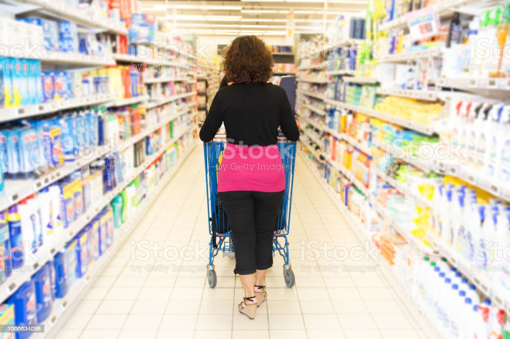 consumer society seen from the back of a woman pushing her cart stock photo