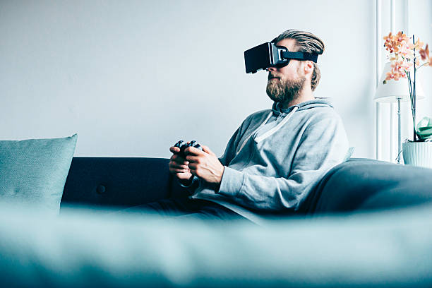Consumer wears VR glasses and plays game at home - Photo