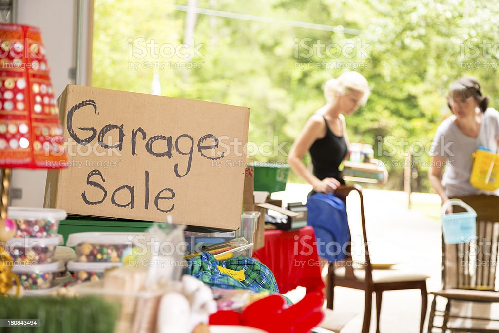 Consumerism:  Adult women shopping at a garage sale in suburbs royalty-free stock photo