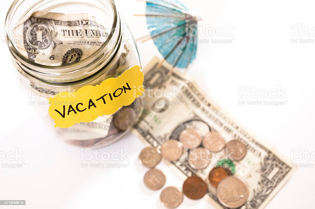 Consumerism:  Money Jar with coins, dollar bills.  Saving for vacation. royalty-free stock photo