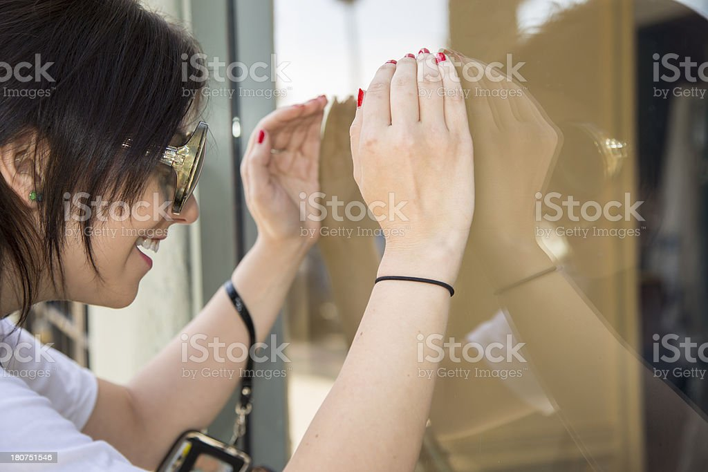 Consumerism:  Woman window shopping peering through cupped hands at display royalty-free stock photo