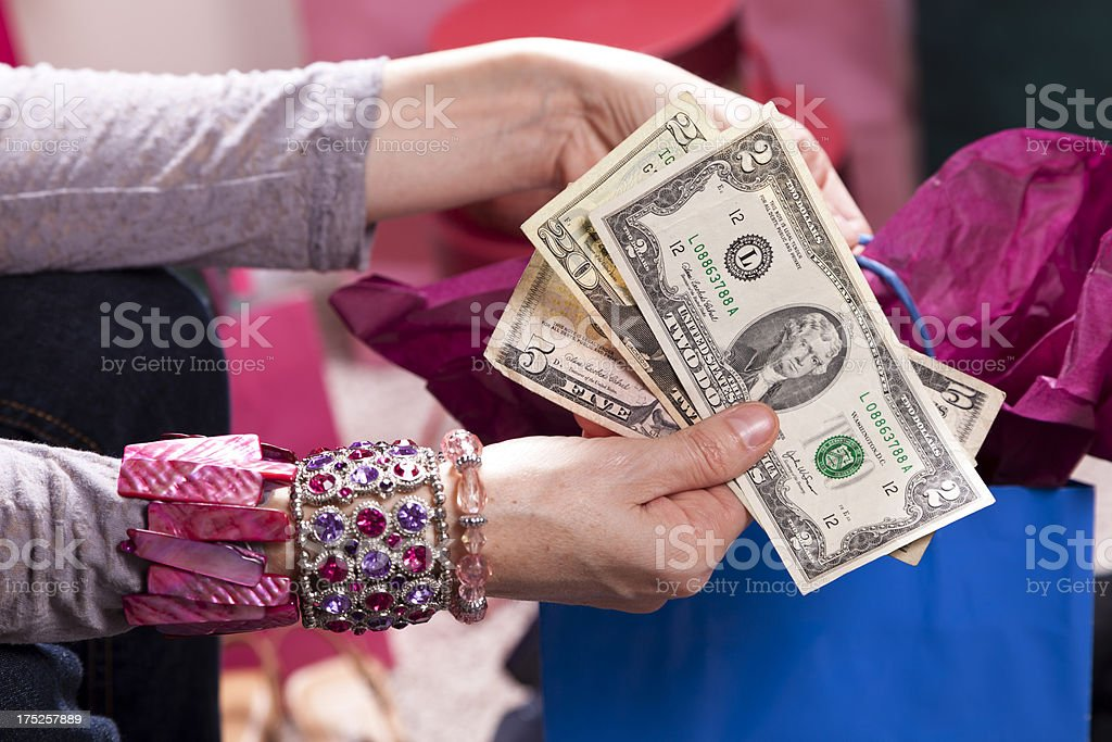 Consumerism.  Woman with money and shopping bag making purchase royalty-free stock photo
