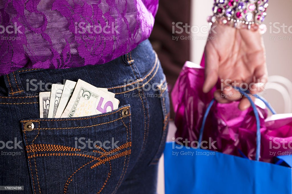 Consumerism.  Woman with money in back pocket and shopping bag royalty-free stock photo