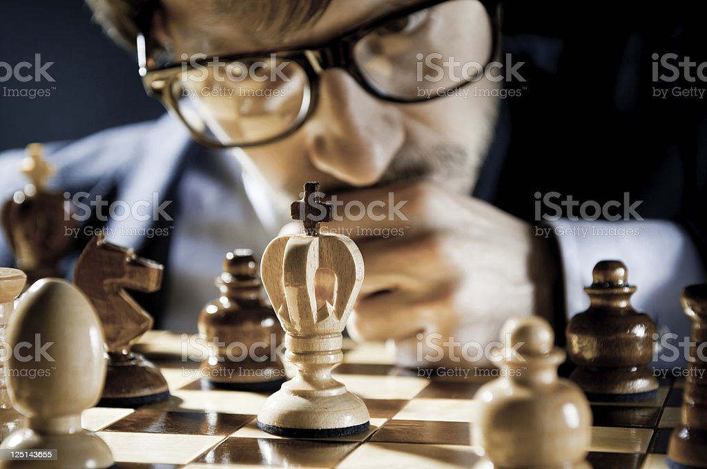 Consummate, focused Chess Player in glasses thinking on next move stock photo