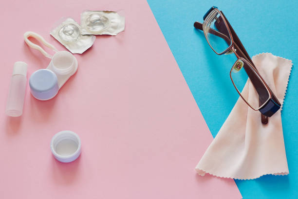 contact lenses, case, glasses and accessories on pink and blue background - contacts imagens e fotografias de stock