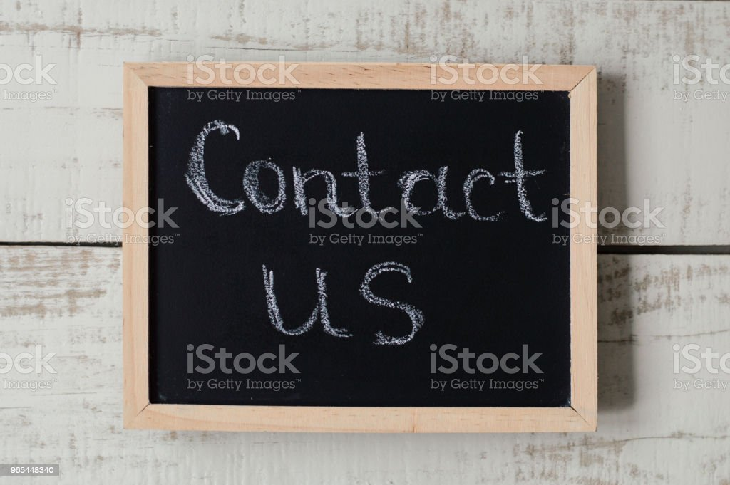 """Contact us banner. Customer support and feedback. Blackboard with text """"Contact us"""" zbiór zdjęć royalty-free"""