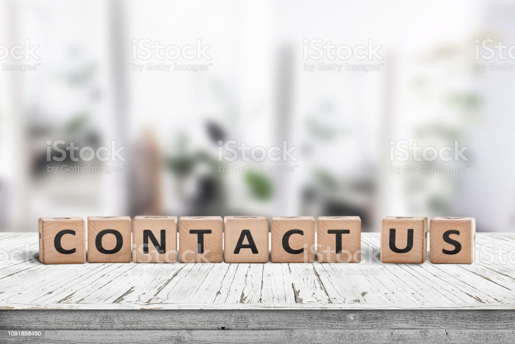 Contact us sign on a wooden desk stock photo