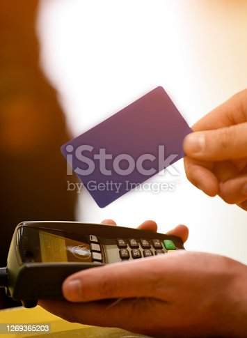 Close up of cashier is using contactless credit card pos terminal to getting the payment.