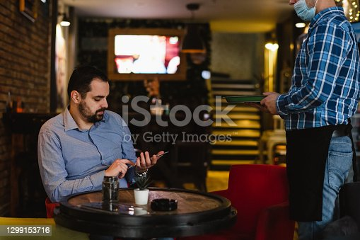 card payment being made between a man and a waiter in a café