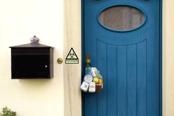 Contactless delivery during the quarantine. Food delivery during the quarantine. Shopping bag with Merchandise, goods and food is hanging at the front door, warning sign, biohazard symbol, message COVID-19 Quarantine. coronavirus neighborhood Assistance stock photo