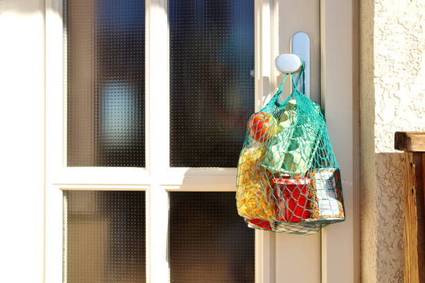 Contactless delivery during the quarantine. Shopping bag with Merchandise, goods and food is hanging at the front door, neighborhood Assistance concept at quarantine time because of coronavirus infection Covid-19 stock photo