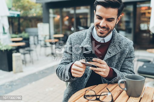Happy elegant young man paying Contactless using credit card and smartphone