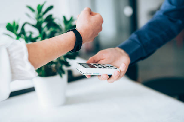 Contactless paying with smartwatch A customer making wireless or contactless payment using smartwatch radio frequency identification stock pictures, royalty-free photos & images