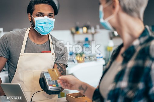 Young barista and Modern woman paying contactless at cafe wearing face protective mask to prevent Coronavirus and other diseases