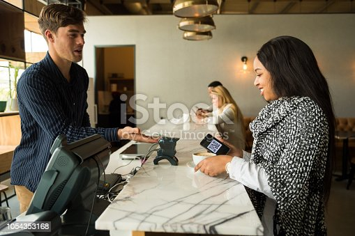 1047669026 istock photo Contactless payment by smart phone 1054353168
