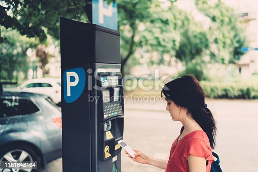 Woman in the city making mobile payment for parking place