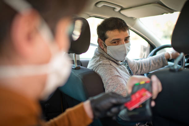 Contactless payment for taxi during an illness epidemic. Taxi driver and his passenger wearing protective masks and gloves
