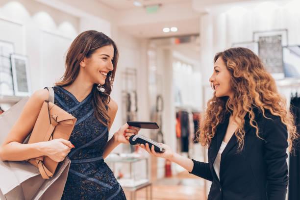 kontaktloses bezahlen in einem luxus-mode-shop - kinderhandtaschen stock-fotos und bilder
