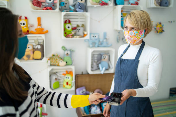 Contactless payment in a small business store during Coronavirus pandemic. stock photo