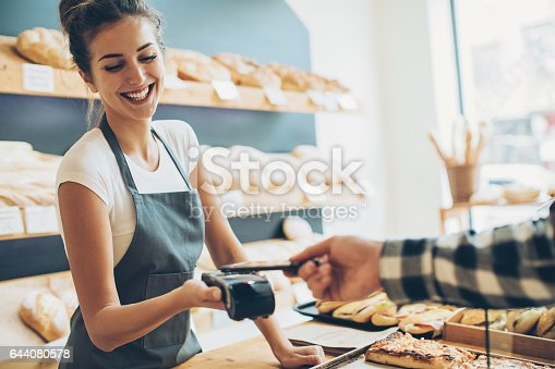 Customer making a contactless payment with his phone in a bakery