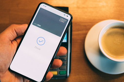 Man in cafe paying contactless with smart phone