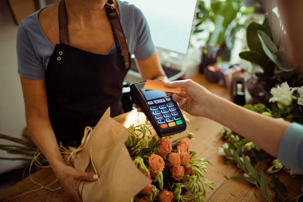 Contactless Payment Close up of a young woman paying for a bouquet with her credit card contactless payment stock pictures, royalty-free photos & images