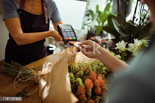 Close up of a young woman paying for a bouquet with her credit card