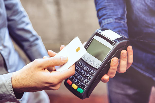 Contactless payment Customer and cashier in a store paying using a contactless card radio frequency identification stock pictures, royalty-free photos & images