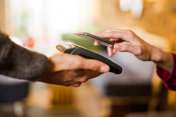 contactless payment using a smart phone hand close up. - pagamento senza contatto foto e immagini stock