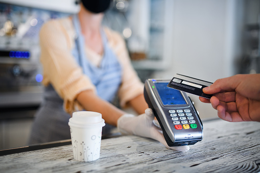 Contactless payment with debit card, coffee shop open after lockdown. Midsection.