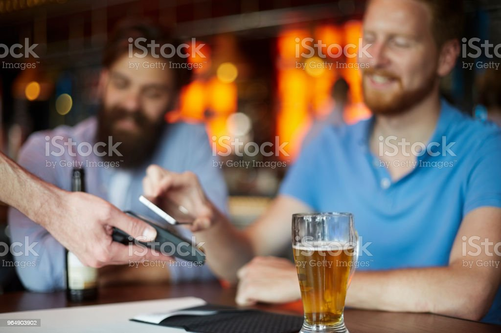 Contactless payment with smart phone in the bar royalty-free stock photo