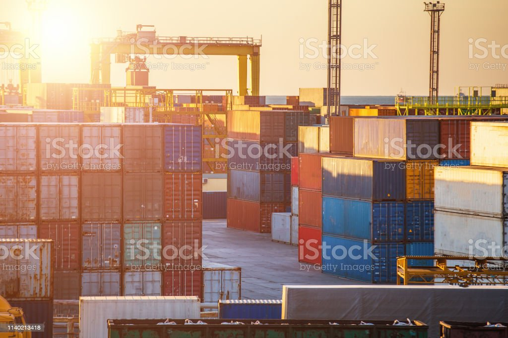 Container boxes in cargo freight ship and industrial port cranes at...