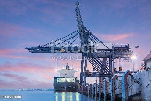 Container Cargo freight ship by crane bridge, logistics harbor at sunrise