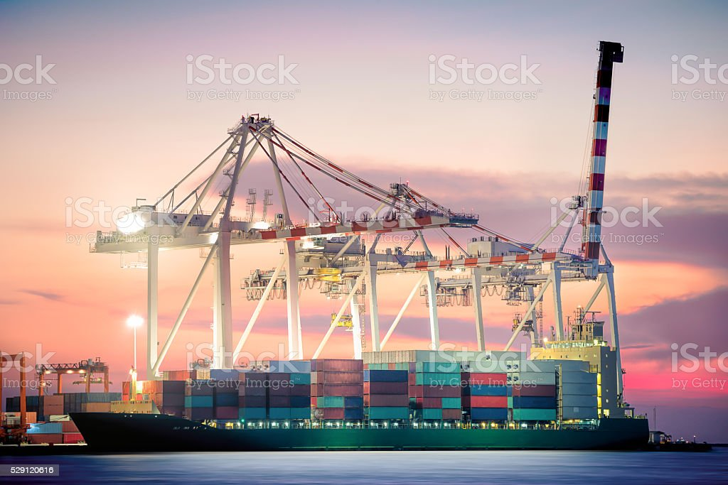 Container Cargo freight ship with working at twilight sky stock photo