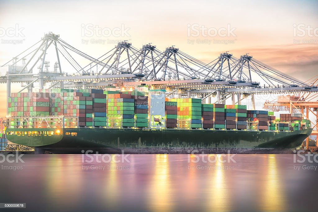 Container Cargo freight ship with working crane at twilight sky stock photo