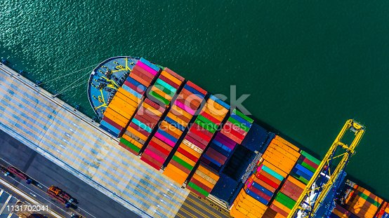 istock Container cargo freight ship with working crane bridge discharge at container terminal, Aerial top view container ship at deep sea port. 1131702041